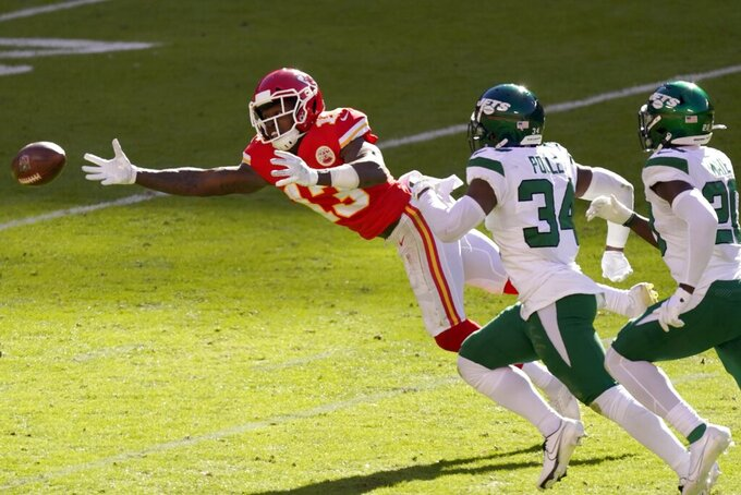 Kansas City Chiefs wide receiver Byron Pringle (13) lays out but is unable to make a catch as New York Jets' Brian Poole (34) and Marcus Maye (20) defend in the first half of an NFL football game on Sunday, Nov. 1, 2020, in Kansas City, Mo. (AP Photo/Charlie Riedel)