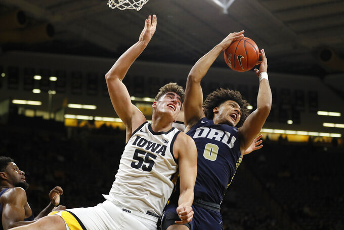 Iowa center Luka Garza (55) fights for a rebound with Oral Roberts forward Kevin Obanor (0) during the second half of an NCAA college basketball game, Friday, Nov. 15, 2019, in Iowa City, Iowa. (AP Photo/Charlie Neibergall)