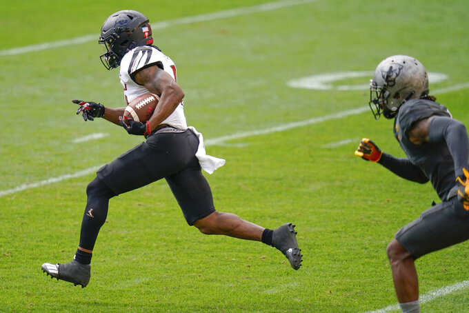 Louisville running back Javian Hawkins, left, dashes away from Pittsburgh defensive back Damar Hamlin, right, on his way to a long touchdown run during the first half of an NCAA college football game, Saturday, Sept. 26, 2020, in Pittsburgh. (AP Photo/Keith Srakocic)