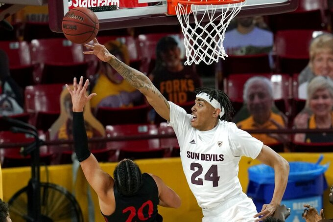 San Diego State guard Jordan Schakel (20) gets off a shot as he is fouled by Arizona State forward Jalen Graham (24) during the first half of an NCAA college basketball game Thursday, Dec. 10, 2020, in Tempe, Ariz. (AP Photo/Ross D. Franklin)