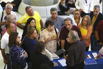 FILE - In this Sept. 18, 2019, file photo people inquire about temporary positions available for the 2020 Census during a job fair designed for people fifty years or older in Miami. On Friday, Dec. 6, the U.S. government issues the November jobs report. (AP Photo/Lynne Sladky, File)
