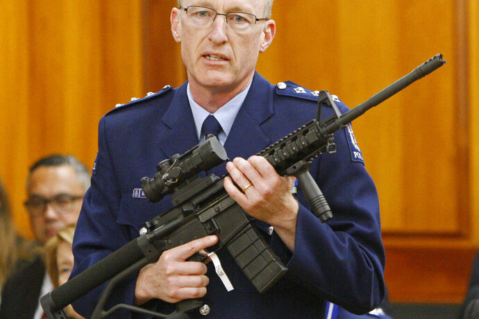 FILE - In this April 2, 2019, file photo, police acting superintendent Mike McIlraith shows New Zealand lawmakers in Wellington, an AR-15 style rifle similar to one of the weapons a gunman used to slaughter 51 people at two Christchurch mosques. Six months after the gunman killed 51 people, New Zealand's government is planning further restrictions to gun ownership. A bill introduced to Parliament on Friday, Sept. 13, 2019 would create a register to track all the guns in the country and require gun owners to renew their gun licenses every five years instead of every 10. (AP Photo/Nick Perry, File)