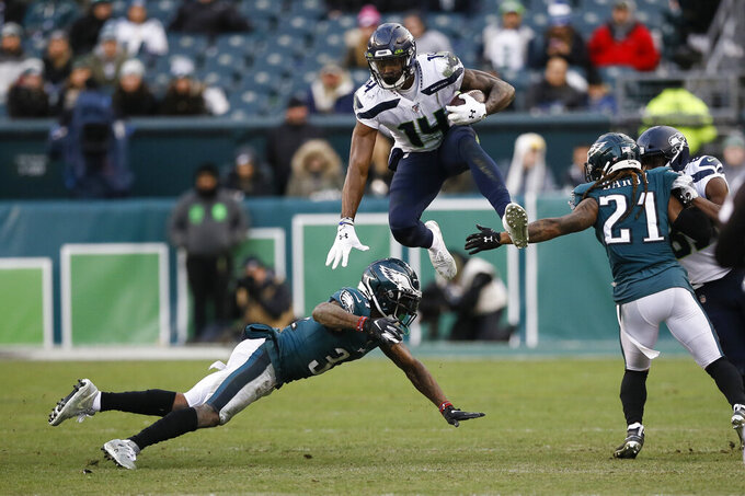 Seattle Seahawks' DK Metcalf (14) leaps past Philadelphia Eagles' Jalen Mills (31) and Ronald Darby (21) during the second half of an NFL football game, Sunday, Nov. 24, 2019, in Philadelphia. (AP Photo/Michael Perez)