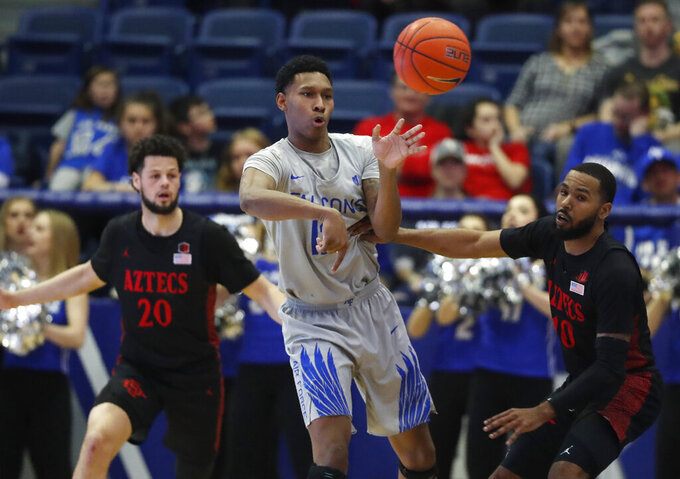 Air Force forward Lavelle Scottie, center, passes the ball as San Diego State guards Jordan Schakel, left, and KJ Feagin defend in the second half of an NCAA college basketball game Saturday, Feb. 8, 2020, at Air Force Academy, Colo. (AP Photo/David Zalubowski)