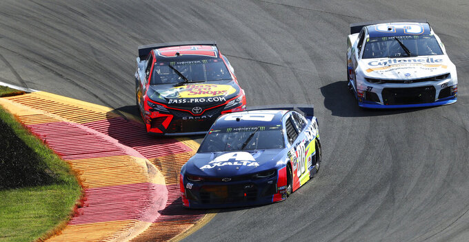 Alex Bowman (88) holds off Martin Truex, Jr., in Turn 1 during a NASCAR Cup Series auto race at Watkins Glen International, Sunday, Aug. 4, 2019, in Watkins Glen, N.Y. (AP Photo/John Munson)