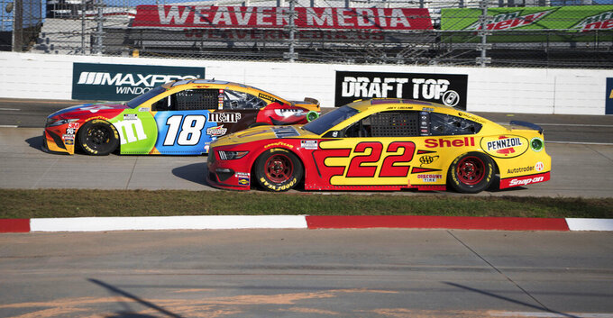 Kyle Busch (18) leads Joey Lagano (22) during a NASCAR Cup Series auto race at the Martinsville Speedway in Martinsville, Va., Sunday, Nov. 1, 2020. (AP Photo/Lee Luther Jr.)