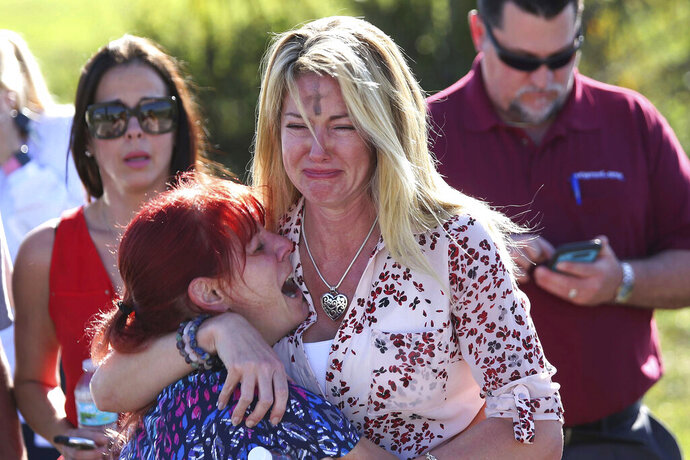 FILE - In this Feb. 14, 2018, file photo, Mechelle Boyle, right, embraces Cathi Rush as they wait for news after reports of a shooting at Marjory Stoneman Douglas High School in Parkland, Fla. The image become emblematic of the Parkland school massacre: two terrified moms outside the school, one of them a tall, weeping blonde with the black smudge of Ash Wednesday on her forehead, the other a petite redhead crying in despair on her shoulder. (AP Photo/Joel Auerbach, File)