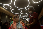 A health worker inoculates a woman against COVID-19 at vaccination center set up inside a shopping mall that remains closed to business in Mumbai, India, Wednesday, Aug. 11, 2021. (AP Photo/Rajanish Kakade)