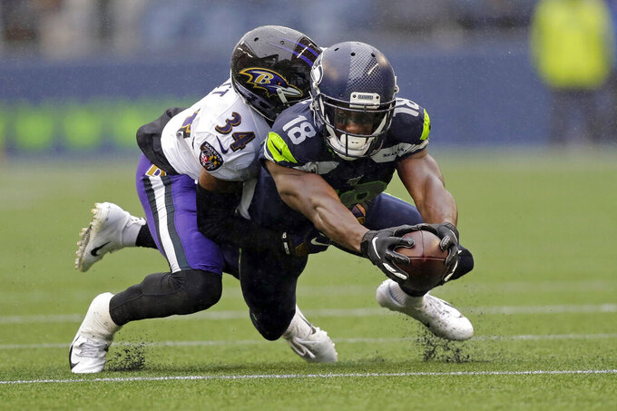Seattle Seahawks wide receiver Jaron Brown (18) reaches for extra yardage as he is tackled by Baltimore Ravens cornerback Anthony Averett (34) during the first half of an NFL football game, Sunday, Oct. 20, 2019, in Seattle. (AP Photo/John Froschauer)