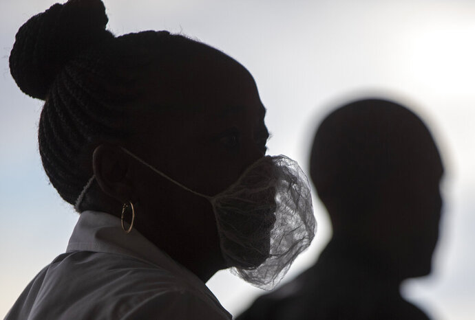 A woman wearing a disposable white beard mask, to protect against coronavirus, stands outside the entrance of a shopping supermarket in Soweto, South Africa, Thursday, March 26, 2020. In just hours, South Africa goes into a nationwide lockdown for 21 days, in an effort to mitigate the spread to the coronavirus. (AP Photo/Themba Hadebe)