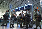 Riot police stand guard at airport express central station in downtown Hong Kong, Saturday, Sept. 7, 2019. Hong Kong authorities were limiting airport transport services and controlling access to terminals Saturday as they braced for a second weekend of disruption following overnight demonstrations that turned violent. (AP Photo/Vincent Yu)