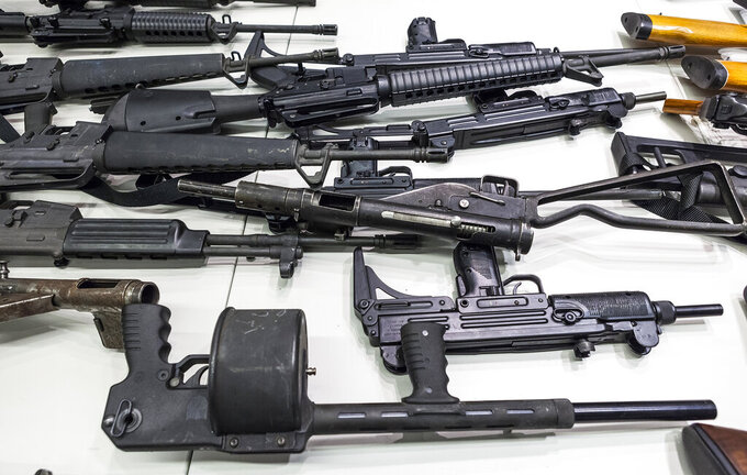 FILE - In this Dec. 27, 2012, file photo are some of the weapons that include handguns, rifles, shotguns and assault weapons, collected in a Los Angeles Gun Buyback event displayed during a news conference at the LAPD headquarters in Los Angeles. A federal judge has overturned California's three-decade-old ban on assault weapons, ruling that it violates the constitutional right to bear arms. U.S. District Judge Roger Benitez of San Diego ruled Friday, June 4, 2021, that the state's definition of illegal military-style rifles unlawfully deprives law-abiding Californians of weapons commonly allowed in most other states. (AP Photo/Damian Dovarganes, File)