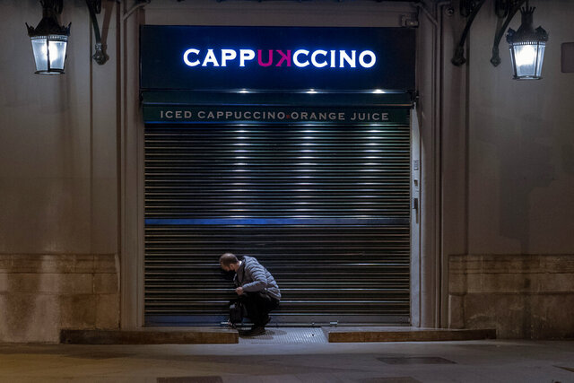 An employee closes his cafeteria before curfew in Barcelona on Monday, Oct. 26, 2020. Spain orders nationwide curfew to stem worsening outbreak. Spanish Prime Minister Pedro Sánchez has declared a second nationwide state of emergency in hopes of stemming a resurgence in coronavirus infections. (AP Photo/Emilio Morenatti)