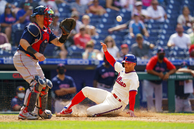 Philadelphia Phillies' Brad Miller, right, slides into home on the sacrifice fly by Andrew McCutchen with Boston Red Sox catcher Christian Vazquez, left, getting the throw during the eighth inning of a baseball game, Sunday, May 23, 2021, in Philadelphia.  (AP Photo/Chris Szagola)