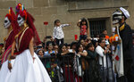 People watch a Day of the Dead parade in Mexico City, Sunday, Oct. 27, 2019. The parade on Sunday marks the fourth consecutive year that the city has borrowed props from the opening scene of the James Bond film,