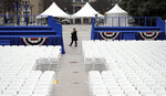 A woman walks across War Memorial Plaza Friday, Jan. 18, 2019, in Nashville, Tenn., where preparations have been made for the inauguration of Tennessee Gov.-elect Bill Lee on Saturday. Lee's inauguration is being moved indoors to the War Memorial Auditorium because of forecasts for weekend rain and thunderstorms. (AP Photo/Mark Humphrey)