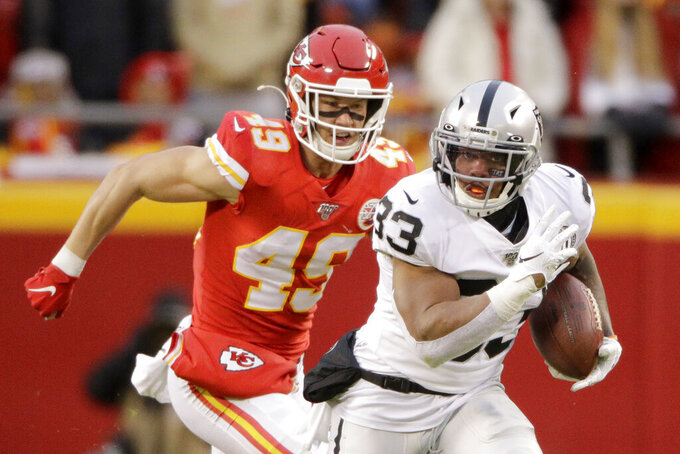 Oakland Raiders running back DeAndré Washington (33) runs away from Kansas City Chiefs safety Daniel Sorensen (49) during the first half of an NFL football game in Kansas City, Mo., Sunday, Dec. 1, 2019. (AP Photo/Charlie Riedel)