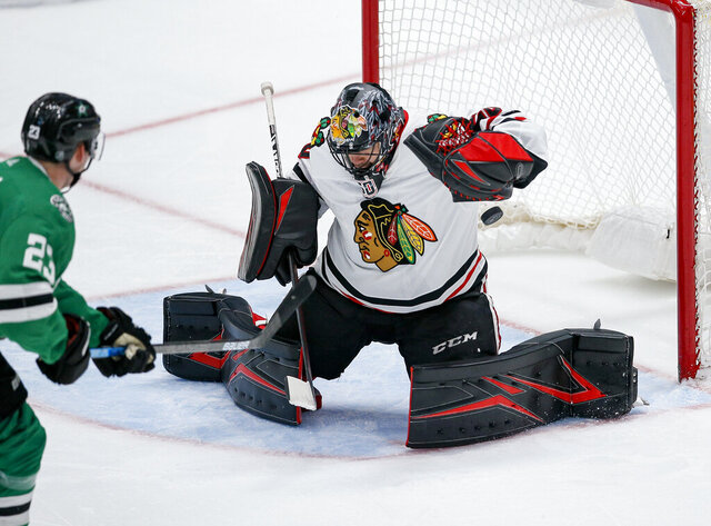 FILE - In this Feb. 23, 2020, file photo, Chicago Blackhawks goaltender Corey Crawford blocks a shot from Dallas Stars defenseman Esa Lindell (23) during the second period of an NHL hockey game in Dallas. Corey Crawford missed the start of training camp with the Blackhawks after he tested positive for COVID-19, leaving the veteran goaltender very little time to prepare for the high-scoring Edmonton Oilers. (AP Photo/Brandon Wade, File)