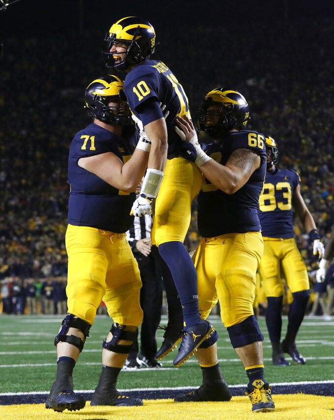 Michigan quarterback Dylan McCaffrey (10) celebrates his 44-yard touchdown run with Andrew Stueber (71) and Chuck Filiaga (66) during the second half of an NCAA college football game against Wisconsin in Ann Arbor, Mich., Saturday, Oct. 13, 2018. (AP Photo/Paul Sancya)