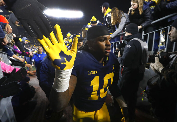 FILE - In this Nov. 17, 2018, file photo, Michigan linebacker Devin Bush (10) walks to the locker room after an NCAA college football game against Indiana, in Ann Arbor, Mich. Devin Bush is skipping his senior season and entering the NFL draft. Bush announced his decision Wednesday, Dec. 19, 2018, on Twitter and Instagram. (AP Photo/Paul Sancya, File)