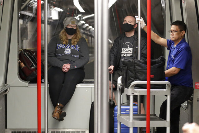 Travelers Meredith Ponder, left, and Coleby Hanisch, both of Des Moines, Iowa, wear masks to remind them not to touch their faces as they ride a train at Seattle-Tacoma International Airport Tuesday, March 3, 2020, in SeaTac, Wash. Six of the 18 Western Washington residents with the coronavirus have died as health officials rush to test more suspected cases and communities brace for spread of the disease. All confirmed cases of the virus in Washington are in Snohomish and King counties. (AP Photo/Elaine Thompson)