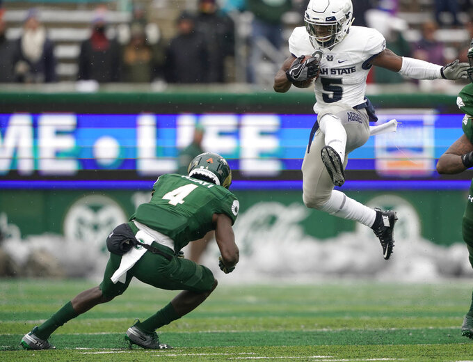 Utah State running back Darwin Thompson (5) jumps over Colorado State cornerback Rashad Ajayi (4) during the first half of an NCAA football game Saturday, Nov. 17, 2018, in Fort Collins, Colo. (AP Photo/Jack Dempsey)