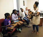 In this Thursday, June 27, 2019 photo, Jocelyn Stovall, of Evolve Music Therapy, sings with special needs students in Montgomery, Ala. (Jake Crandall/Montgomery Advertiser via AP)