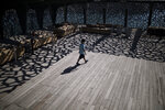 A boy walks along the roof of Marseille's MUCEUM during a hot day in Marseille, southern France, Friday Aug 7, 2020. France has warned the public to prepare for a heatwave as temperatures were set to rise to 42 degrees Celsius (107 Fahrenheit) in parts of the country. (AP Photo/Daniel Cole)
