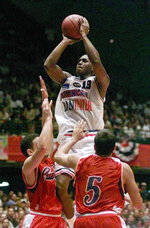 "FILE - In this Sunday, July 18, 1999, file photo, the Dominican Republic's Felipe Lopez (13) gets above Puerto Rico defenders Eddie Casiano (5) and Edgar Padilla, left, as he shoots during the second half of an Olympic basketball qualifier, in San Juan, Puerto Rico.  Lopez, once the top-rated player in the nation in high school, could never live up to the lofty expectations in college or the NBA. His story is told in the new film ""The Dominican Dream."" (AP Photo/Tony Gutierrez, File)"