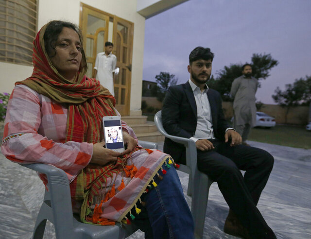 Kaneez Sughra, wife of kidnaped prominent Pakistani journalist Matiullah Jan, shows a picture her husband to journalists while other family member gather at a family's home, in Islamabad, Pakistan, Tuesday, July 21, 2020.  Jan, known for his hard hitting criticism of the country's powerful institutions, including its military, is missing, human rights groups and a family member said Tuesday. (AP Photo/Anjum Naveed)