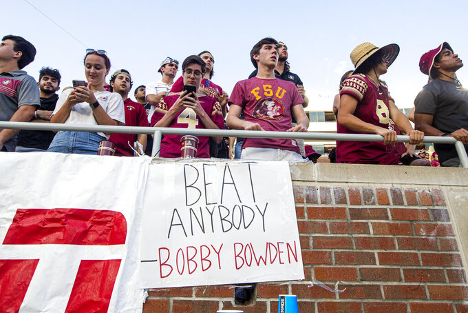 Bored Florida State fans look at their phones over a Bobby Bowden quote in the second half of an NCAA college football game against Louisville in Tallahassee, Fla., Saturday, Sept. 25, 2021. Louisville defeated Florida State 31-23. (AP Photo/Mark Wallheiser)