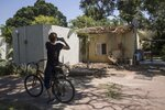 A woman takes a photo of a house damaged by a missile fired from Gaza Strip, in a kibbutz near the Israel and Gaza border, Thursday, Aug. 9, 2018. Israeli warplanes struck dozens of targets in the Gaza Strip and three people were reported killed there, while Palestinian militants from the territory fired scores of rockets into Israel in a fierce burst of violence overnight and into Thursday morning. (AP Photo/Tsafrir Abayov)