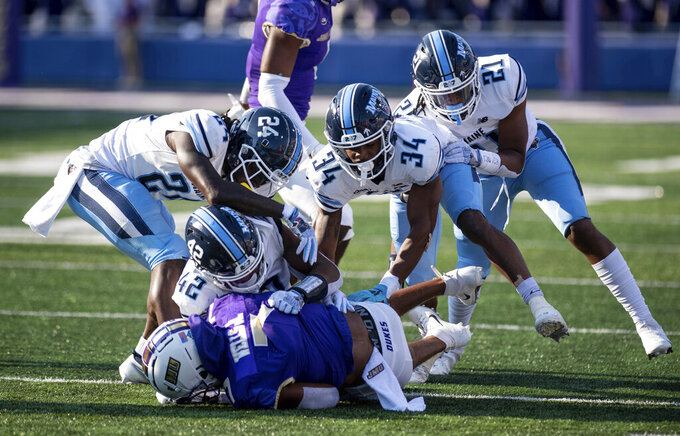 James Madison wide receiver Antwane Wells Jr. (7) is brought down by Maine defenders during the first half of an NCAA college football game in Harrisonburg, Va., Saturday, Sept. 11, 2021. (Daniel Lin/Daily News-Record via AP)