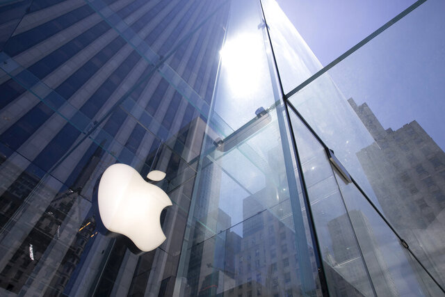 "FILE - In this June 16, 2020, file photo, the sun is reflected on Apple's Fifth Avenue store in New York. Apple will cut its app store fee in half from 30% to 15% for most developers beginning Jan. 1, the biggest change in its commission rate since the app store began in 2008. The fee reduction will apply to developers who made up to $1 million from the app store in 2020, which is the ""vast majority"" of developers in the store, Apple said. (AP Photo/Mark Lennihan, File)"