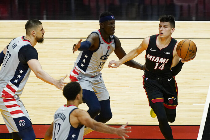 Miami Heat guard Tyler Herro (14) looks to pass the ball surrounded by Washington Wizards center Alex Len (27), guard Jerome Robinson (12) and forward Isaac Bonga (17), during the second half of an NBA basketball game, Friday, Feb. 5, 2021, in Miami. (AP Photo/Marta Lavandier)