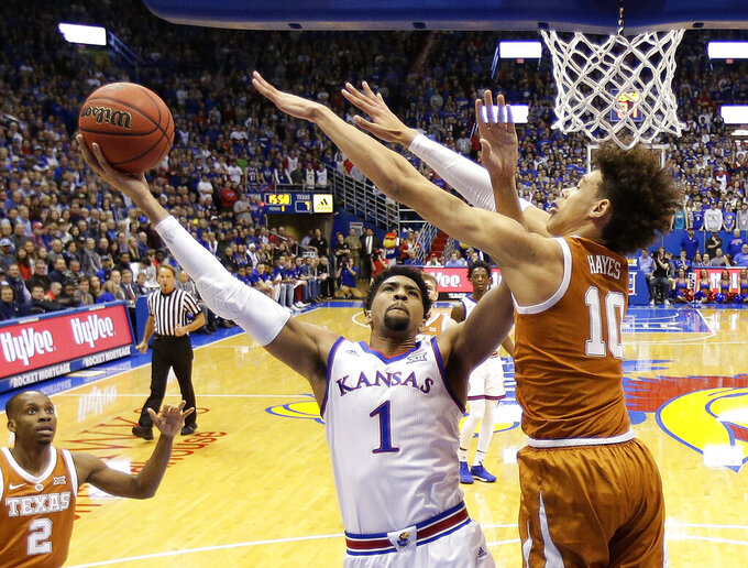 FILE - In this Jan. 14, 2019, file photo, Kansas forward Dedric Lawson (1) shoots under pressure from Texas forward Jaxson Hayes (10) during the first half of an NCAA college basketball game, in Lawrence, Kan. Lawson was named the Big 12 Conference Newcomer of the Year, Tuesday, March 12, 2019.(AP Photo/Charlie Riedel)