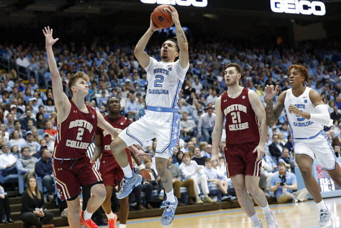 North Carolina guard Cole Anthony, center, drives to the basket while Boston College guard Julian Rishwain, left, and forward Nik Popovic (21) defend during the first half of an NCAA college basketball game in Chapel Hill, N.C., Saturday, Feb. 1, 2020. (AP Photo/Gerry Broome)