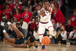 St. John's Rasheem Dunn, right, chases down a loose ball as West Virginia's Gabe Osabuchien tumbles on the court in the second half of an NCAA college basketball game, Saturday, Dec. 7, 2019 in New York. St. John's won 70-68. (AP Photo/Mark Lennihan)