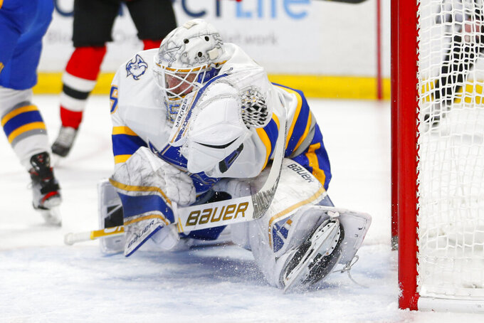 Buffalo Sabres goalie Linus Ullmark makes a glove save during the first period of the team's NHL hockey game against the New Jersey Devils, Thursday, Feb. 25, 2021, in Buffalo, N.Y. (AP Photo/Jeffrey T. Barnes)