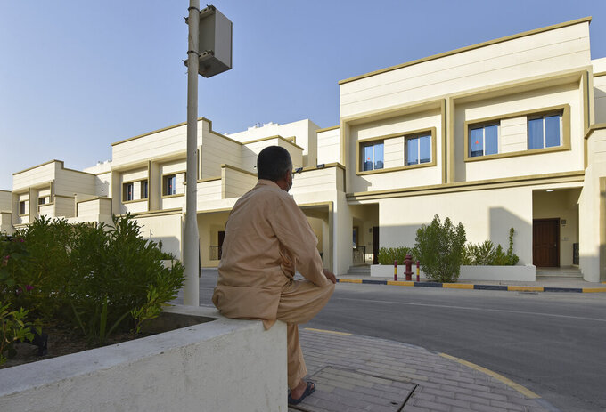 An Afghan man who was evacuated from Kabul sits on a wall at a temporary housing complex in Doha, Qatar, Aug. 21, 2021. Qatar played an out-sized role in U.S. efforts to evacuate tens of thousands of people from Afghanistan. Now the tiny Gulf Arab state is being asked to help shape what is next for Afghanistan because of its ties with both Washington and the Taliban insurgents now in charge in Kabul. (Qatar Government Communications Office via AP)