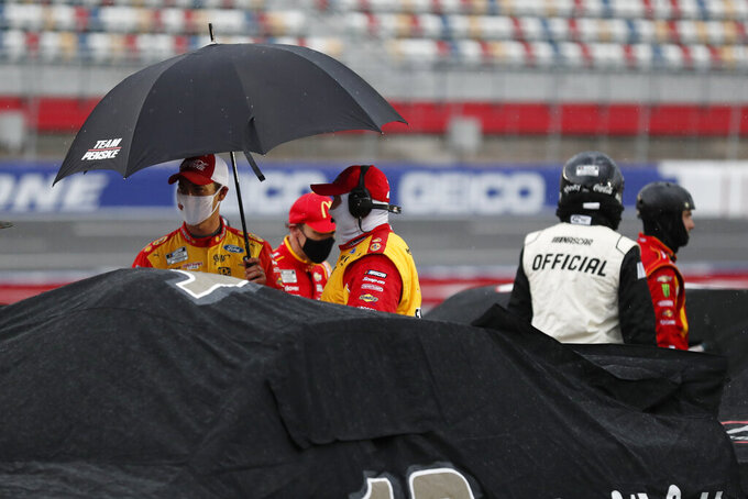 Driver Joey Logano, left, stands with an umbrella during a rain delay at a NASCAR Cup Series auto race at Charlotte Motor Speedway Sunday, May 24, 2020, in Concord, N.C. (AP Photo/Gerry Broome)