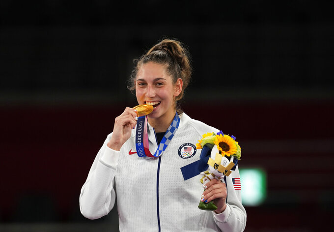 United States's Anastasija Zolotic holds her gold medal during a ceremony for the taekwondo women's 57kg at the 2020 Summer Olympics, Sunday, July 25, 2021, in Tokyo, Japan. (AP Photo/Themba Hadebe)
