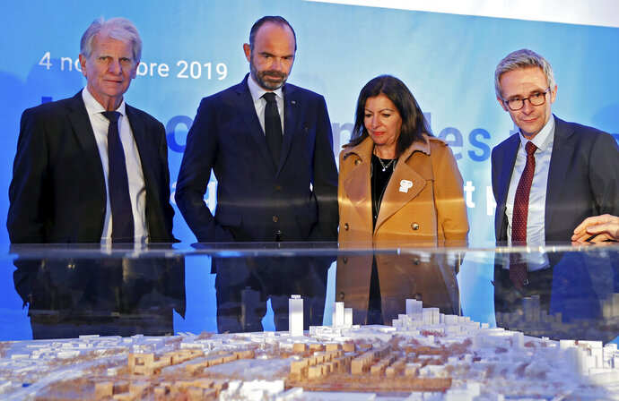 FILE - In this Monday Nov. 4, 2019 file photo, French Prime Minister Edouard Philippe, second left, and Mayor of Paris Anne Hidalgo look at an architectural model as they attend a ceremony to mark the start of the construction of Paris 2024 Olympic Village in Saint-Ouen, near Paris. A partnership deal signed by the IOC with Airbnb has sparked the ire of French hoteliers, who have suspended their collaboration with Paris 2024 Olympics organizers over fears the agreement sealed with the platform will create unfair competition. (Gonzalo Fuentes, Pool via AP, File)