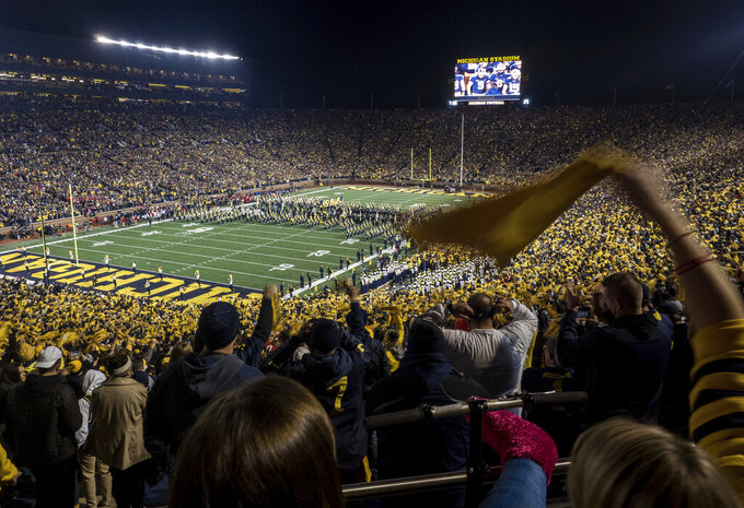 FILE - In this Oct 13, 2018, file photo, fans cheer as the Michigan football team takes to the field at Michigan Stadium before an NCAA college football game against Wisconsin in Ann Arbor, Mich. Two people have been arrested for flying a drone over Michigan Stadium during the Wolverines' 2019 football season opener against Middle Tennessee State on Saturday, Aug. 31, 2019. (AP Photo/Tony Ding, File)