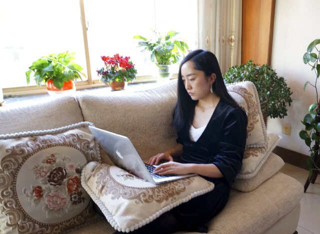 In this Wednesday, Feb. 12, 2020, photo released by Maggie Zhang, Zhang uses a laptop computer at her parents' home in in the northwestern city of Zhangye in Gansu province. Zhang, founder of SheTalks, a company in Beijing that organizes events for women, is working out of her parents' apartment after she went back for the Lunar New Year and said she might stay through March. (Maggie Zhang via AP)