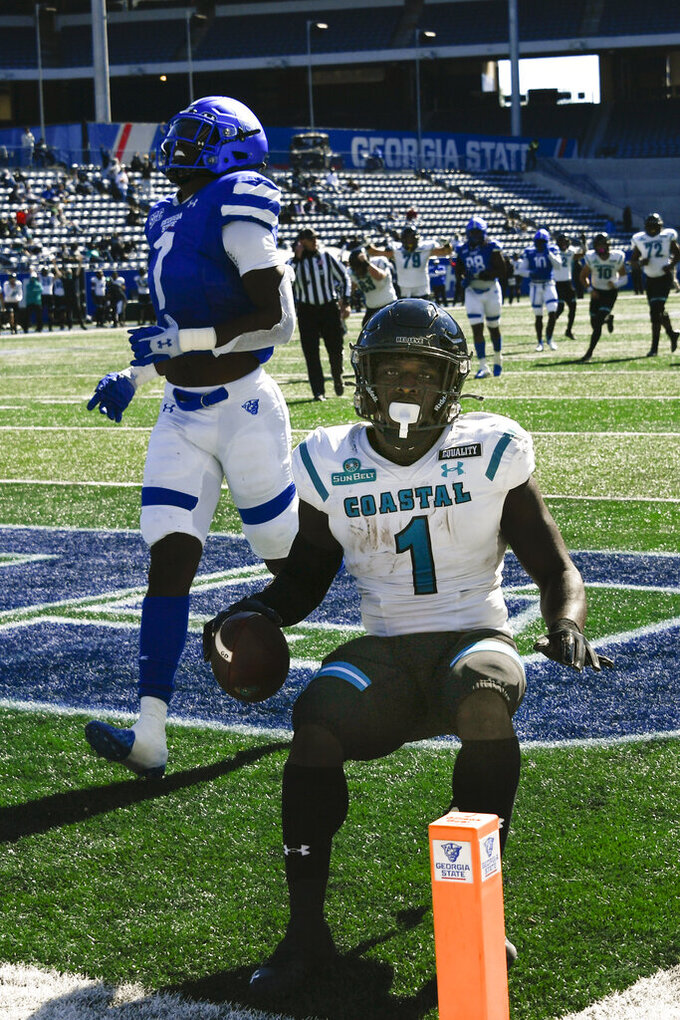 Coastal Carolina running back CJ Marable scores a touchdown on a reception in front of Georgia State linebacker Jordan Strachan (7) during the first half of an NCAA football game Saturday, Oct. 31, 2020, in Atlanta. (AP Photo/John Amis)