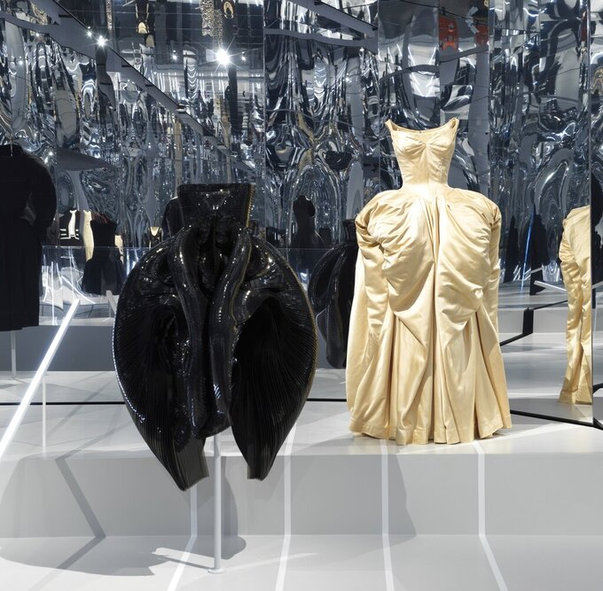 """This image released by the Metropolitan Museum of Art in New York shows a black dress by Dutch designer Iris Van Herpen, left, and a ball gown by American designer Charles James, part of The Costume Institute's exhibition """"About Time: Fashion and Duration,"""" tracing 150 years of fashion. (Anna-Marie Kellen/Metropolitan Museum of Art via AP)"""