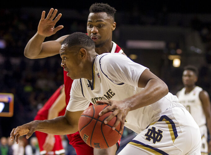 Notre Dame's D.J. Harvey, front, drives against North Carolina State's Torin Dorn during the first half of an NCAA college basketball game, Saturday, Jan. 19, 2019, in South Bend, Ind. (AP Photo/Robert Franklin)