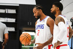 Los Angeles Clippers forwards Kawhi Leonard, left, and Paul George pose for photos during the NBA basketball team's media day in Los Angeles, Sunday, Sept. 29, 2019. (AP Photo/Ringo H.W. Chiu)