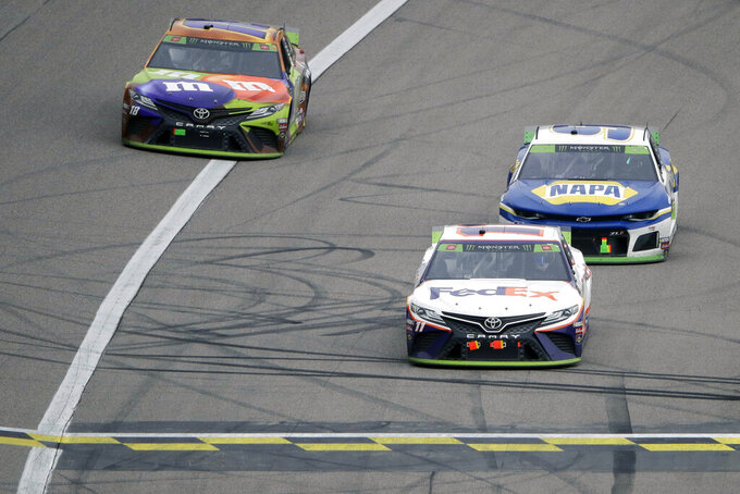 Denny Hamlin, front right, crosses the finish line ahead of Chase Elliott, back right, and Kyle Busch to win a NASCAR Cup Series auto race at Kansas Speedway in Kansas City, Kan. Sunday, Oct. 20, 2019. (AP Photo/Charlie Riedel)